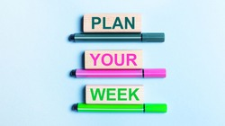 On a light blue background, there are three multi-colored felt-tip pens and wooden blocks with the PLAN YOUR WEEK text.