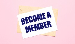 On a light pink background - a craft envelope. It has a white sheet of paper that says BECOME A MEMBER