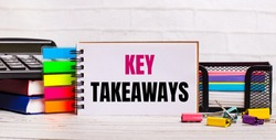 On a light wooden background, a calculator, multi-colored sticks and a notebook with the text KEY TAKEAWAYS. Business concept