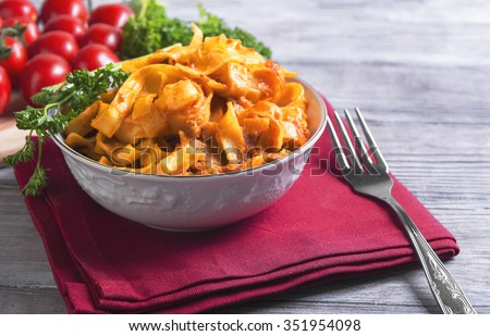 On a light wooden background in vintage style food dinner plate with Bolognese Tagliatelle pasta, cherry tomatoes on a branch, fork, napkin, towel red, green curly parsley