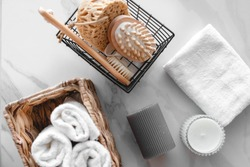 On a marble background a set of various bath accessories. Terry towel, soap, comb, oil, shampoo, loofah washcloth and candles. The view from the top