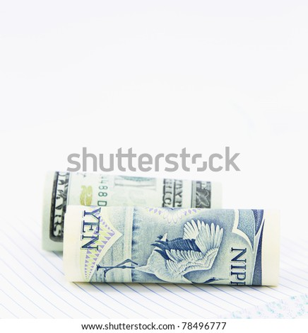 On a notebook with lined pages, two currencies, the dollar and yen, are positioned together in close up image
