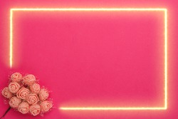 On a pink background, a gold frame for Valentine's Day with a decor of paper pink roses. Horizontal photo