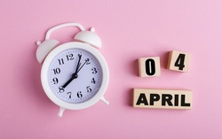 On a pink background, a white alarm clock and wooden cubes with the date of APRIL 04