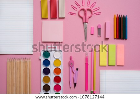 On a pink background, school accessories and a pen, colored pencils, a pair of compasses, a pair of compasses, a pair of scissors. Copy space, top view #1078127144