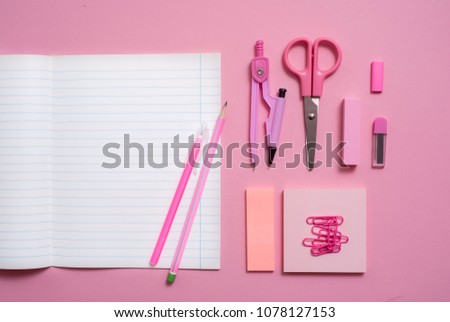 On a pink background, school accessories and a pen, colored pencils, a pair of compasses, a pair of compasses, a pair of scissors. Copy space, top view #1078127153