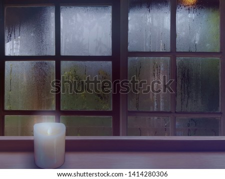 On a rainy day, see the water drops on the outside mirror blurred. (a rainy day window background) On the left wooden floor Place candles in white. Feelings, sadness, loneliness, nostalgia. #1414280306
