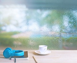 On a rainy day, seeing a drop of water on the outer glass blurred (Background, rainy day window) On the table, place a cup of coffee, glasses, diary, books, pen and blue music headphones. (Sadness)