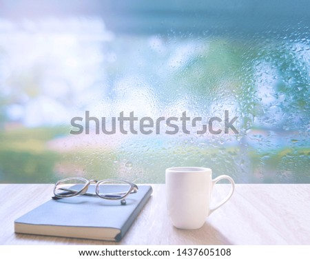 On a rainy day, seeing a drop of water on the outer glass blurred (Background, rainy day window) On the table, place a cup of coffee, glasses and diary. Feelings, sadness, loneliness, nostalgia. #1437605108