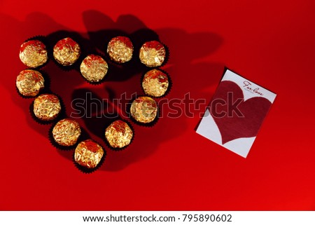 On a red background is a box in the shape of a heart and in it is candy in a Golden wrapper. Next lay a piece of paper with a cartoon heart #795890602