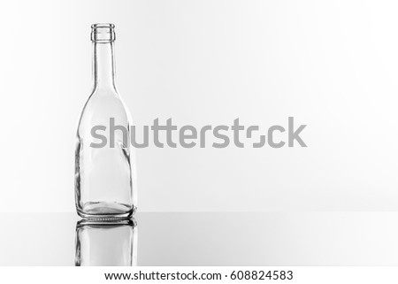 On a reflective tile is an empty transparent bottle #608824583