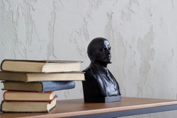 on a shelf is a stack of old books next to a bust of Lenin