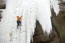 On a snowy winter day an ice climber ascends the frozen waterfall in Tonty Canyon, Starved Rock State Park, LaSalle County, Illinois.