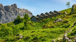On a steep slope there is a row of goat stalls from alpine farming, staggered and adapted to the slope in such a way that the avalanche cannot destroy them in winter. behind  are steep rocky mountains