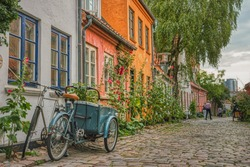 On a summer day a typical Danish Cargo bike, better known as Christiania Bike, is parked at the entrance of a house in a cosy, cobbled street conveying coziness and cultural concept - Aarhus, Denmark