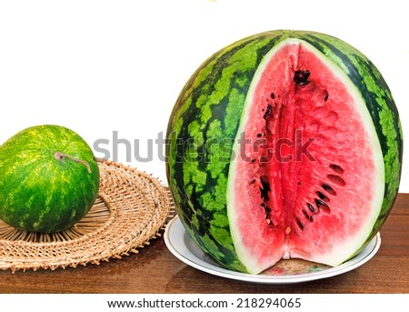 On a table surface on a dish the cut water-melon is located. It is presented on a white background.