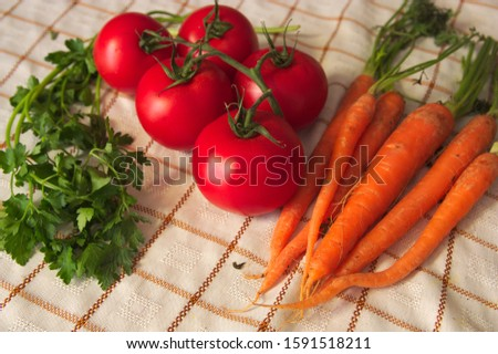 On a table we see a set of vegetables, carrots, some tomatoes, some parsley branches all seen from above, flat lay