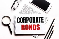 On a white background glasses, a magnifier, pencils, a smartphone and a notebook with the text CORPORATE BONDS