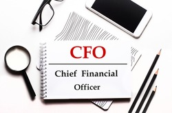 On a white background glasses, a magnifier, pencils, a smartphone and a notebook with the text CFO Chief Financial Officer