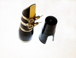 On a white background in the collection of the mouthpiece, the ligature and the mouthpiece of a clarinet. Close up.