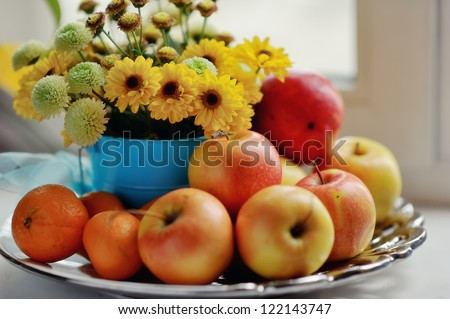 on a white background ripe apples, mandarin bright bouquet of autumn flowers in the window
