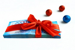 On a white background Russian bills of two 2000 thousand rubles, tied with a red ribbon with a bow. Christmas balls.