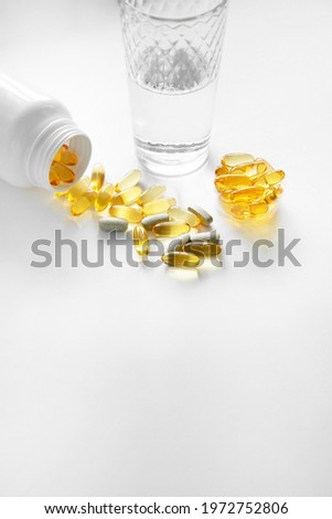On a white background with a glass of water and a nearby spoon of Olekapsula (zachte capsules) voedingssupplementen: visolie, omega-3, omega-6, omega-9, vitamin A, vitamin D3, vitamin E, teunisbloemol Stockfoto ©