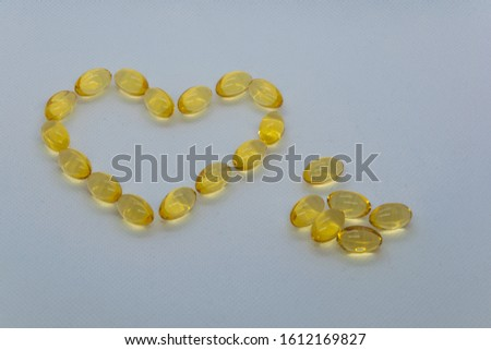 On a white background yellow capsules. form a heart, next to a group of yellow capsules