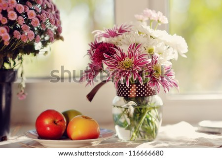 on a white plate ripe apples and bright bouquet of autumn flowers