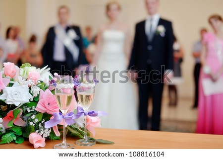 on a white table the wedding bouquet lies and nearby there are glasses