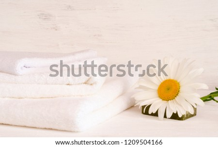 On a white wooden background is a clean white towel with a white large chamomile (flower). The concept of the resort, cleanliness
