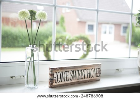 on a window sill in the house is a sign with the text home sweet home #248786908