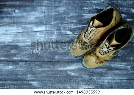 On a wooden background a pair of brown shoes. One pair of leather sneakers is very worn. Black Friday - time to buy new sneakers. Sneakers in the upper right corner are laced with laces. Close-up #1498935599