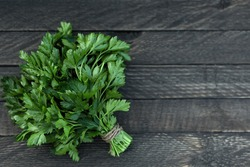 On a wooden background is a bunch of green fresh fragrant parsley.