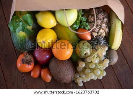 On a wooden table a paper bag full of lots of freshly picked fresh fruit. Many vitamins together on a wooden table.