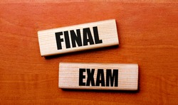 On a wooden table are two wooden blocks with the text FINAL EXAM
