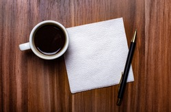 On a wooden table next to a white cup of coffee and a pen is a clean white paper napkin. Copy space