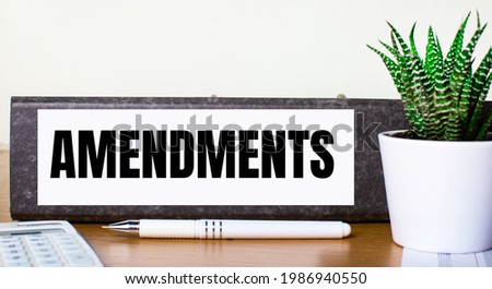 On a wooden table there is a folder for documents with a AMENDMENTS dough, a green plant in a pot, a pen and a calculator. Business concept. Foto stock ©