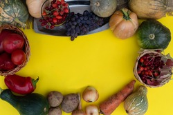 On a yellow background lie vegetables, fruits and berries - wild rose, viburnum, grapes, tomatoes, peppers, pumpkins, potatoes, onions, carrots.