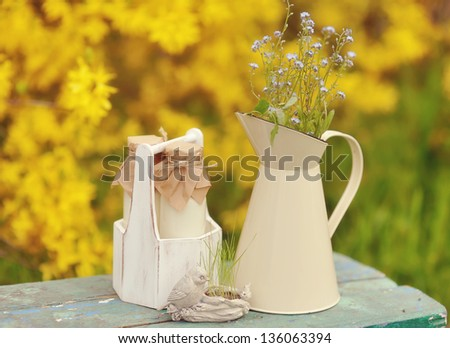 on a yellow background with a jug of wild flowers and bottles