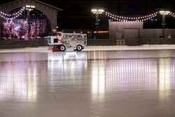 On an open ice skating rink, lit with festive lights and garlands, a combine recovers ice for ice skating.