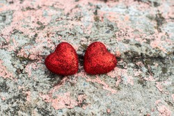 on an pink old concrete, brick wall, two shiny red hearts. valentine's day postcard. top view. space for text, Flat lay