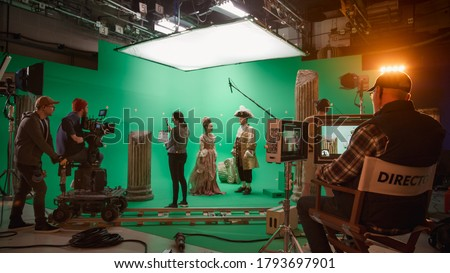 Photo of  On Big Film Studio Professional Crew Shooting History Costume Drama Movie. On Set: Director Controls Cameraman Shooting Green Screen Scene with Two Actors Talented Wearing Renaissance Clothes Talking