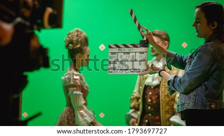 On Big Film Studio Professional Crew Shooting Period Costume Drama Movie. On Set: Camera Assistant Using Clapperboard, Cameraman Shooting Green Screen Scene with Two Actors in Renaissance Clothes