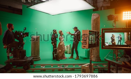 On Big Film Studio Professional Crew Shooting Period Costume Drama Movie. On Set: Director Explains Scene to Woman Actress Playing Renaissance Lady and Actor Wearing Motion Capture Suit
