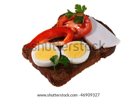 On black bread the cut boiled egg, bacon slice, a tomato and red pepper with a parsley leaf lies.