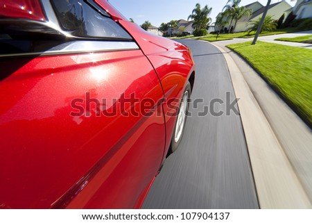 On board camera shot of a red car traveling at speed down a suburban street. - stock photo