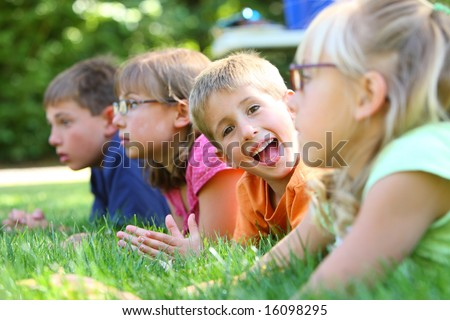 On boy looking at camera in group of kids - stock photo