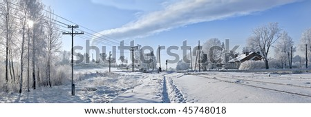 On branches plentiful hoarfrost. The shining sun shines sideways. Near to small town. The railway