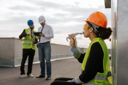 On construction site beautiful smiling African lady engineer drinking some water from bottle on the rooftop of building she wearing safety helmet and yellow safety glasses